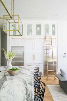 Modern white kitchen boasts a ladder on a brass rail fixed beneath glass front cabinets and over stainless steel refrigerators recessed into white cabinetry finished with brass hardware. Glass Front Cabinets, Built In Cabinets, Dream Home Design, House Design, Built In Bunks, Ceiling Storage, Wood Steps, How To Dress A Bed, Stone Countertops