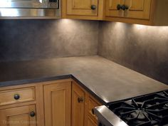 Concrete countertop w/concrete backsplash... Task lighting... Concrete  Backsplash