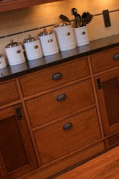 Jim Walker chose to mix plain and quarter-sawn oak in the kitchen cabinets. The tile backsplash, electrical covers and cabinetry hardware are copper-colored to reflect the Arts and Crafts style.