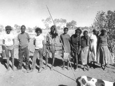 The Pintubi Nine pose awkwardly shortly after their arrival in Kiwirrkurra in 1984. Warlimpirrnga Tjapaltjarri is holding the spear; Yukultji Napangati is third from right.