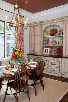 A cheery breakfast area overlooks the backyard and pool. G&J table and chairs mix with a built-in cabinet that has been given a distressed, whitewashed look.