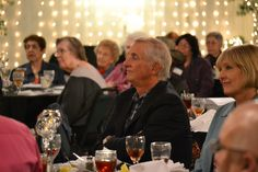 Ken Rector, Warm Springs Foundation, and Debbie Billa, WellMed Foundation, look onward as awards are presented to OASIS volunteers.