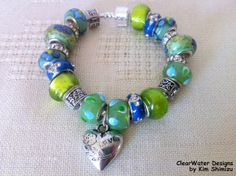 European Style Bracelet Large Bead Bracelet by ClearWaterDesignsbyK on Etsy, $29.95 This adorable European Large Bead bracelet is packed full with gorgeous High End Blue & Green European Lampwork Beads. This versatile bracelet has some Chinese Cloisonné (enamel) beads & Enamel Rhonedells . I've also used lots of Rhinestone Rhondelles for extra glitz to make this an Upscale Bracelet. The Puffed Heart Charm is Acrylic with Silver Tones.