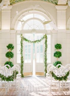 Lovely light and airy ceremony space, decorated with green topiaries and garlands. #wedding #decor