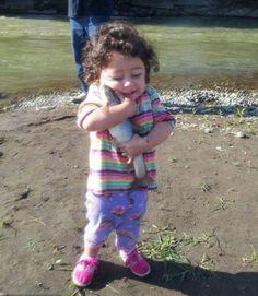 小女孩滿足地擁抱一條被她救起的魚兒..