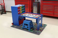 Tez Gilmir, who has constructed amazing things like the Alfa Romeo Mailbox and this Soundwave eletrician's toolbox, has turned his creative eye to his son's Lego obsession. The above portable Lego creation station is the end result, with bins for brick organization, a great table for building and finished with some cool 3D-printed Lego studs.