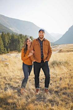 Fall Engagement Session - Red Lodge - Montana - Beartooth Pass - Beartooth Highway - Man - Woman - Engaged - Couple - Fiancé - Outdoor - Mountains - Field - Trees - Dirt Road - Rocks - Grass - Brown - Gold - Orange - Sweater - Plaid Shirt - Jacket - Jeans - Blue Baseball Cap - Montana Wedding Photographer - Sara Nagel Photography