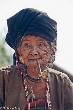 An Akhu woman, wearing a turban & plug earrings and smoking a corn cob pipe, in Wan Jai.