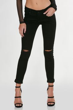 Skinny jeans with rocker style. Distressed and ripped at knee holes and below pockets. Classic five pocket design with zip closure.