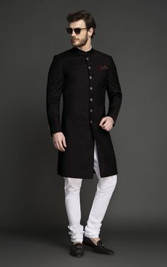 Black Achkan is the cornerstone of every mans wardrobe. Tailored & designed for an ambitious modern man, this Achkan features interesting tailoring details over bling and will make you look every bit elegant and sophisticated. Indian Wedding Suits Men, Mens Indian Wear, Mens Ethnic Wear, Indian Groom Wear, Wedding Dress Men, Indian Men Fashion, Mens Fashion Suits, Mens Suits, Man Fashion