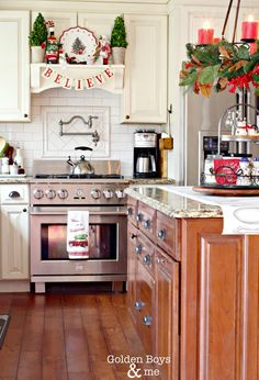 Christmas decor in kitchen with DIY mantel hood and candle chandelier over island-www.goldenboyandme.com
