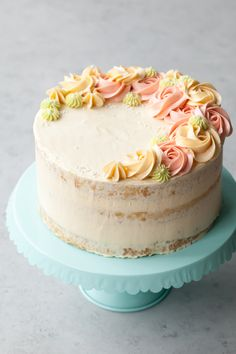 """Fluffy coconut cake soaked with a coconut simple syrup and adorned with spirals of pastel vanilla bean buttercream. Instead of weighing down the subtle coconut flavor with thick slabs of frosting or muting it with vibrant tropical flavors, the semi """"naked"""" frosting allows the coconu"""