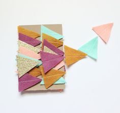 This cute garland is sewn from hand cut felt and glitter cardstock triangles (two glued back to back so that there is glitter on both sides). You