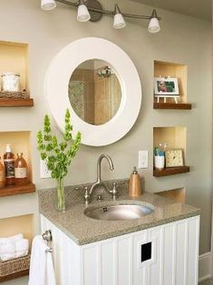 Square niches carved out between wall studs provide storage and display space, and the series of squares is broken up with a chic round mirror. by neva