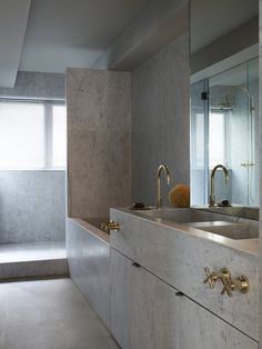 Gold hardware and fixtures paired with cool grey marble. Bathroom design for Two Two Six Hollywood Road in Hong Kong by Ilse Crawford.