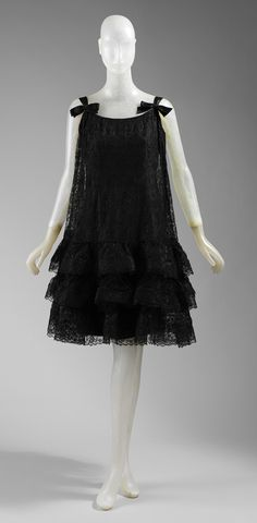 Cristobal Balenciaga: Black lace 'Baby Doll' mini evening dress (1965) This short evening dress of black lace consists of three layers. The first layer is a built-in bra supported by six bones, two in front and back, one at each side. The second layer is a slip of cream-colored silk with a sheer black chiffon overlay. The slip is shaped like a sheath and has a wide band of lace at the hem. The outer layer consists of a loose-fitting baby-doll dress with a triple tier of ruffles on the skirt.