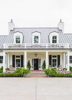 The front porch is anchored by symmetrical planters, hedges and flowers.