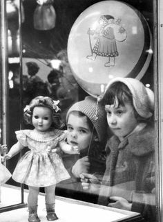 Reminds me of mom, sister, me and my dolls..... This is a photo of children at the shop window at Christmas time, 1956.