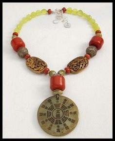 1 of a kind! Hand carved Tibetan jade calendar pendant hangs from necklace made of Moroccan copal resin beads, hand carved antiqued bovine bone beads, handmade Tibetan silver beads, handmade Tibetan Jade repousse capped beads, Red Jasper and natural Korean jade beads. Beautiful colors in this necklace! Fastens with my signature, large, fancy handforged sterling silver clasp and chain. Adj from about 20 - 22 inches.