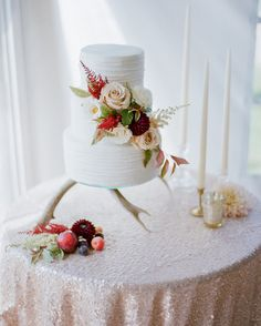 This couple picked a chocolate wedding cake for their September wedding in Montana. Joyce Dye of Just Desserts frosted the three-tiered confection with vanilla buttercream, then decorated it with an off-center grouping of flowers. For an extra autumnal touch, red plums, crab apples, and candles were placed on top of the sparkly linen in front of the cake.