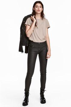 Een legging van elastisch imitatieleer met een doorgestikte pas bij de knieën. De legging heeft een lage taille, een zichtbare ritssluiting en fake zakken v