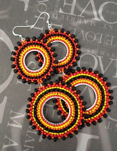 Beadwork boho 70s style long double hoop earrings earrings with shades of red, yellow, orange and black 11/0, 8/0 and 6/0 seed beads. The french hook earwires and findings are 14kt gold plated. Gorgeous hoop earrings that will receive tons of compliments. The double hoops are joined with 14kt gold plated closed jump rings. Each bead is individually expertly woven to make these beautiful earrings. The french hook earwires are sterling silver and the center hoop is silver plated.  These large…