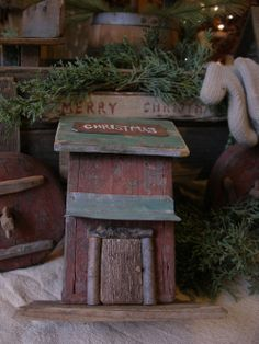 Love Christmas!!! Cute primitive house for your Christmas vignette. These are limited as the old green wood on the roof is very limited as it is a piece of wood we found in an old barn.  Newly made from new and old wood. Painted in aged drab red milk paint. Old green worn wood for the roof. Old green painted tin door overhang. Stick framed door with pegged door knob. Hand painted rusty tin Christmas sign. Measures 5 7/8 tall. Wood base is 4 5/8 across by 3 1/2 deep. $29 plus shipping.