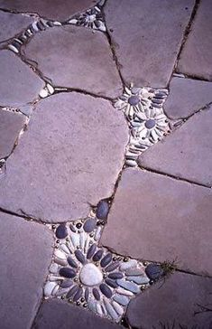 Fun patio idea for the cracks in between the stones on the pathway to door, I likey! 乱形石張りの隙間に丸平石を盾に敷き詰めて花の様な模様をあしらう。