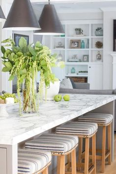Blue and beige striped saddle counter stools sit in front of a light gray kitchen island fitted with white and gray marble countertops illuminated by Three Goodman Hanging Lamps.