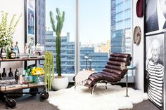 """Plush leather pieces like this 1940s M. Baughman-style <a href=""""http://www.timothyoulton.com/products/living/furniture/armchairs/bilbao-chair.html  """">Bilbao lounge chair</a> and luxurious sheepskin come together for this perfect nook overlooking the view from the 28th-floor windows."""