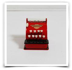 """Ancienne petite caisse enregistreuse couleur rouge des années 60 en métal.  Marque française. Les différentes touches permettent aux montants de s'afficher, la touche """"total"""" déclenche l'ouverture du tiroir.  Traces et rayures d'usage mais très bel état général.Taille: 12,5 cm de haut, 12 cm de large.Retrait sans frais : Entrez le code ATELIER à la fin de votre commande"""