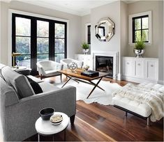 White trim, black doors and windows; Black mullions; cabinets on either side of fireplace; gray couch