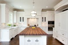 butcher block island, rounded edges preferred cabinets, lights, island and granite all in white with wood to match hardwood on island.... , love the legs on the cabinets. Love both countertops and the pure white cabinets (not sure either is practical).... Dark island top and floors with white cabs... Would want more glitzy lighting though