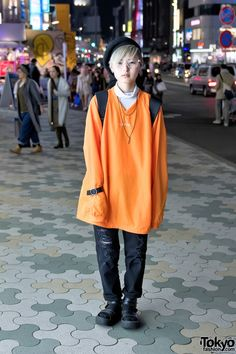Pyon is a 19-year-old student who we met on the street in Harajuku. This is not the first time that we've street snapped Pyon. Pyon is wearing an orange extra-long sleeve top from LIBITUM ad LIB with ripped jeans from the Japanese streetwear brand MYOB NYC and black Tokyo Bopper platform sandals with black socks. Pyon's accessories – from Faith Tokyo and Mineral – include a black beret, lots of earrings, clear frame glasses, a string necklace, a leather o-ring bracelet, and a Chance Chance…