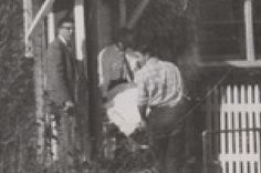 """Uno de los cuerpos  es retirado de la escena del crimen. Duane West, como Fiscal de Distrito, observa el traslado. Me pregunto de quien sería. ¿Herbert? ¿Bonnie? ¿Nancy? ¿Kenyon? Que tragedia. Ampliación de la fotografía aparecida en la primera plana de """"The Garden City Telegram"""" el lunes 16 de noviembre de 1959."""