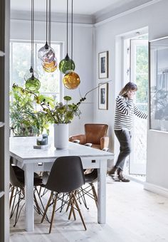 Bright dining room with a marble dining table surrounded by Eames chairs. We love the colorful pendants.