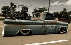 1964 1965 1966 slammed C10 pickup with custom door graphics, patina finish, and a vintage bike in the bed.