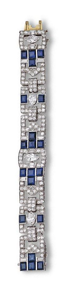 SAPPHIRE AND DIAMOND BRACELET, CIRCA 1930.  The articulated strap designed as a series of stylized buckles, set at intervals with 4 marquise-shaped diamonds weighing approximately 4.40 carats, 8 baguette and 4 trapeze-cut diamonds weighing approximately 2.50 carats, 152 round diamonds weighing approximately 12.00 carats, further decorated with 20 rectangular sapphires weighing approximately 18.00 carats, mounted in platinum, length 7 inches.