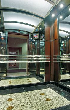 This elevator was installed at 160 Bloor East | for Oxford Property Group. It utilizes an arched stainless steel ceiling and wall to wall glass mirror panels.