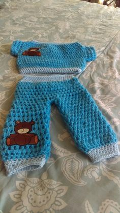 A boy clothes top and bottom with a trimming that is baby blue with a bear on it