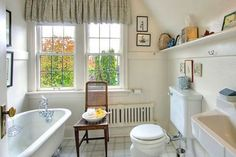 like old style toilet and tub, shelves and low profile radiator