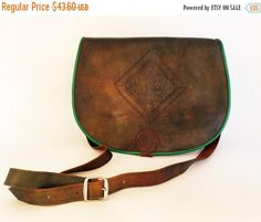 This vintage leather satchel is druidic chic, in earthy tones of brown and green, and with enough pockets to be prepared for any natural calling. Buckles at bottom front.  Brand: Unknown Era: 80s or 90s Condition: very good, has a few scuffs on the front Fiber content: leather Country of origin: unknown