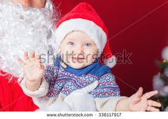 Closeup happy baby and Santa Claus waiting for gift or present. Child dressed in red Santa hat. Xmas and New Year holiday!