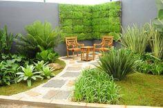 Wall garden of grass, shrubs, Guzmania ligulata, Rhapis excelsa, Licuala grandis.