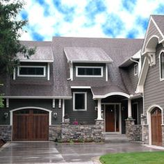 Everything about this exterior I love. Color paint + wood garage + stonework = gorgeous.