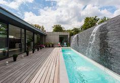 grande piscine étroite avec cascades, plage en bois composite et buis en boule