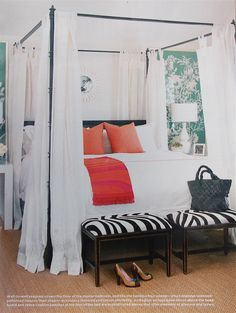 Black canopy bed white curtains green wallpaper black and white ottomans