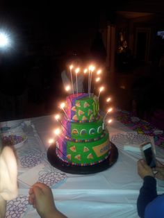 Kids split birthday party tiered birthday cake that was one side Ninja turtles and other half Hello Kitty. Sparkler candles down the sides to separate it