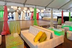 "For the Central Park Conservancy's annual ""Taste of Summer"" event in New York, designer Marc Wilson punched up the all-white furnishings with drapes and throw pillows in bright pink, green, and yellow hues."