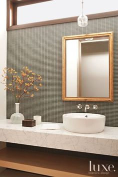 Gray and gold accent a powder room with a glass mosaic backsplash and a marble countertop, both by Ann Sacks. The mirror is a find from Lucca Antiques. The pendant light is by Alison Berger Glassworks.